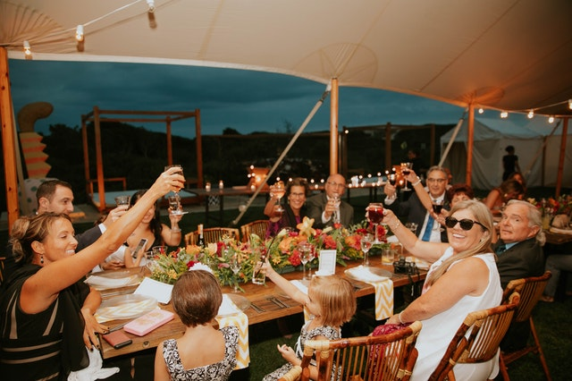 A large table of people outside eating with some raising glasses in a toast